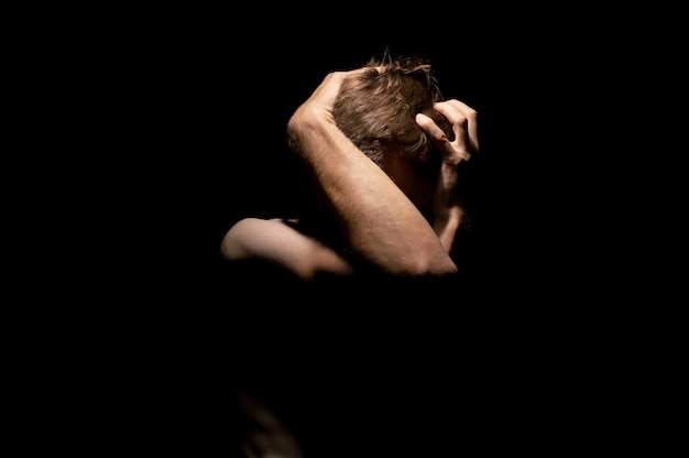 Mains sur la tête, photo dramatique en noir et blanc d'un homme