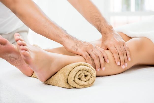 Mains de thérapeute masculin donnant un massage à une jambe de femme