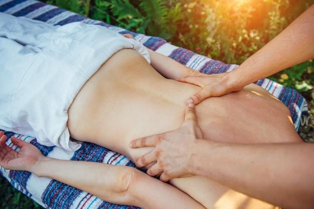 Mains de thérapeute masculin faisant massage à la jeune patiente qui se trouve sur la table de massage à l'extérieur. gros plan sur le massage des épaules et du dos. focus sur les mains du masseur