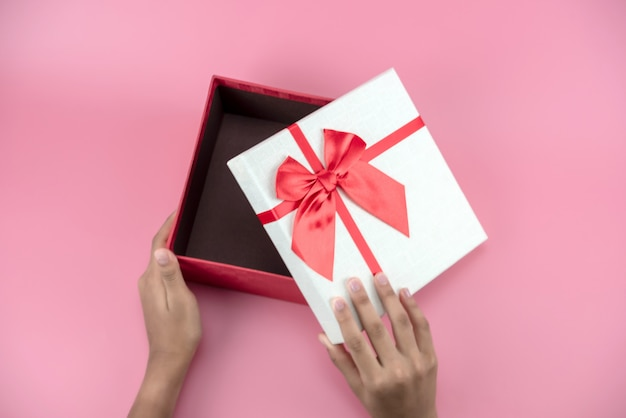 Les mains tiennent une boîte cadeau rouge et blanche vide