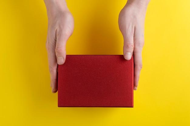 Mains tiennent la boîte en carton rouge, vue de dessus. copiez l'espace. maquette.
