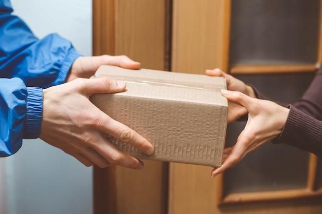 Les mains tiennent une boîte de livraison.
