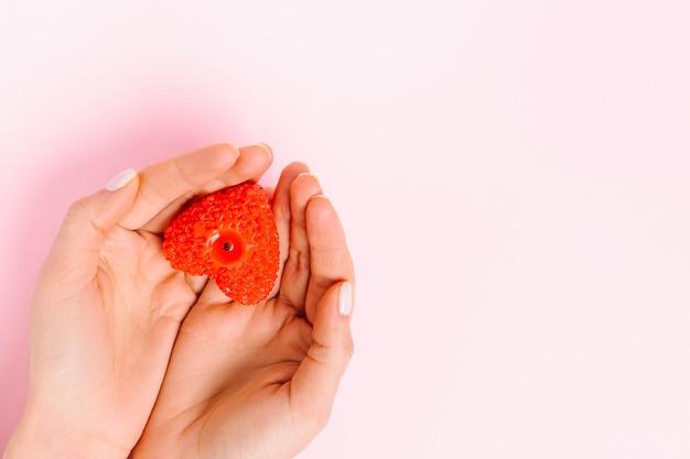 Les mains tiennent une bougie en forme de cœur. fond rose et espace latéral vide où pourrait se trouver votre annonce. saint valentin, charité.