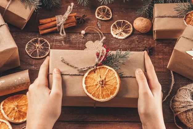Les mains tiennent un cadeau de noël emballé dans du papier kraft et des matériaux naturels. concept de nouvel an vert
