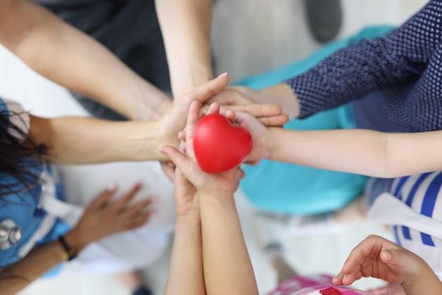 Les mains tiennent le coeur rouge