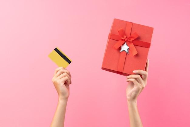 Les mains tiennent des coffrets cadeaux rouges et des cartes bancaires sur un mur rose