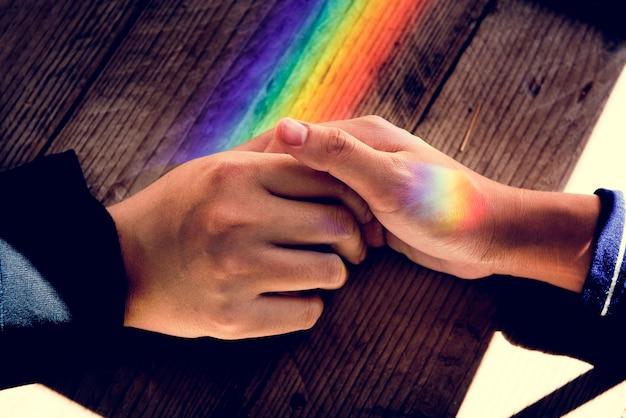 Mains tiennent ensemble avec des lumières de prisme