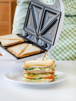 Les mains tiennent un grille-pain avec des tranches de pain frais frites près d'un sandwich prêt sur la plaque blanche
