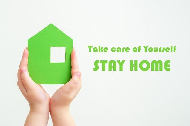 Les mains tiennent la maison de papier vert.