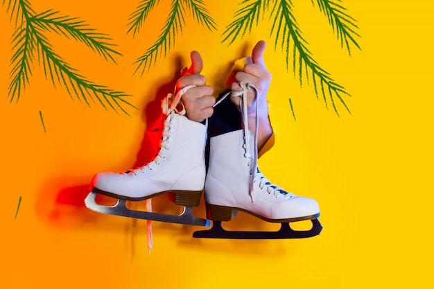 Les mains tiennent les patins d'hiver par les lacets. ils dépassent du trou sur le fond de papier jaune et sont éclairés par des néons
