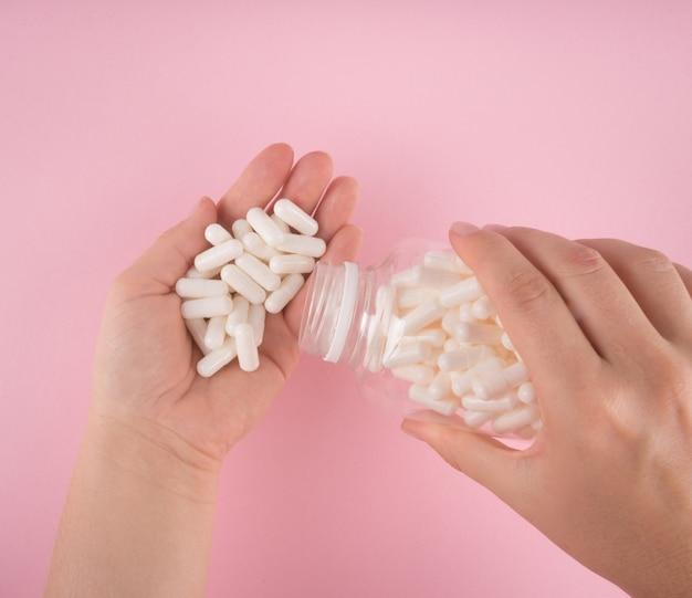Mains tiennent des pilules isolées sur fond de couleur pastel. médicaments et pilules sur ordonnance fond plat.