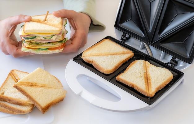 Les mains tiennent un sandwich frais cuit avec du fromage, du bacon et des légumes près du toster sur la table blanche.