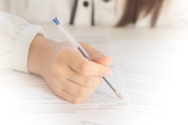 Les mains tiennent un stylo sur du papier et remplissent un test en gros plan