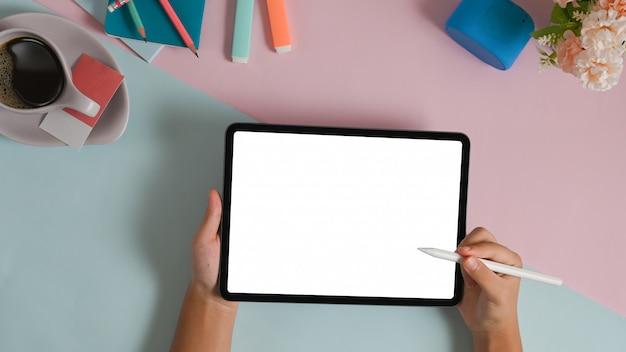 Les mains tiennent une tablette à écran blanc blanc et un stylet sur une table bicolore