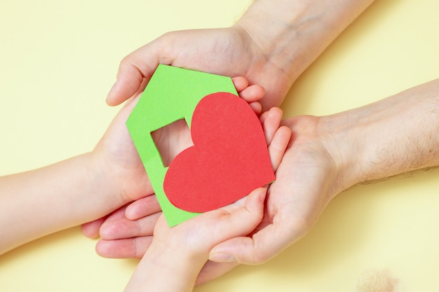 Mains tient maison de papier vert avec coeur rouge
