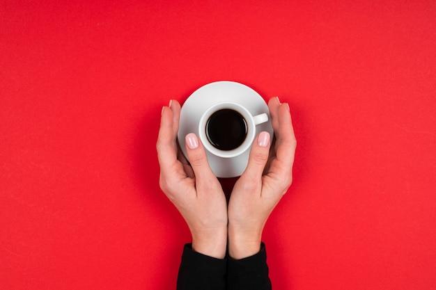 Mains tient une tasse de café isolé sur rouge