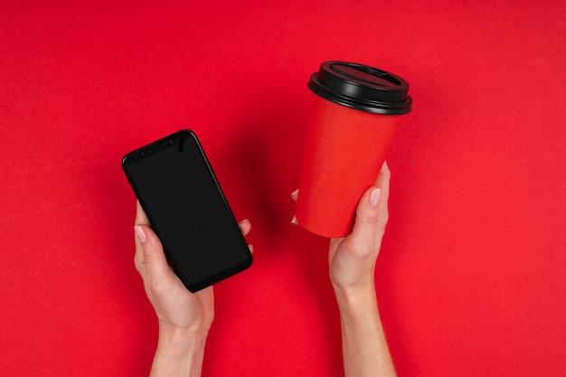 Mains tient une tasse de café et téléphone isolé sur rouge