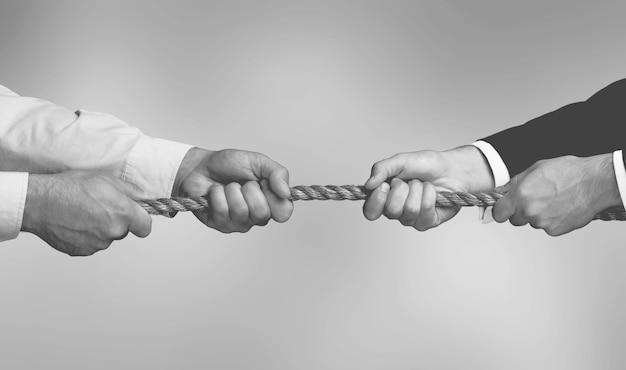 Mains tirant la corde jouant à la corde, les gens sont compétitifs, différends, concept de concours.