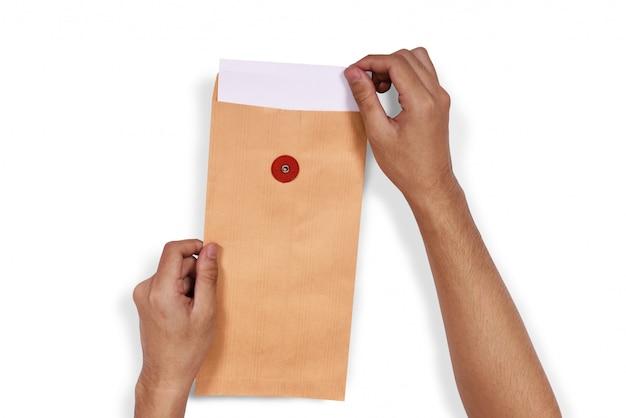 Mains tirer le papier blanc de l'enveloppe