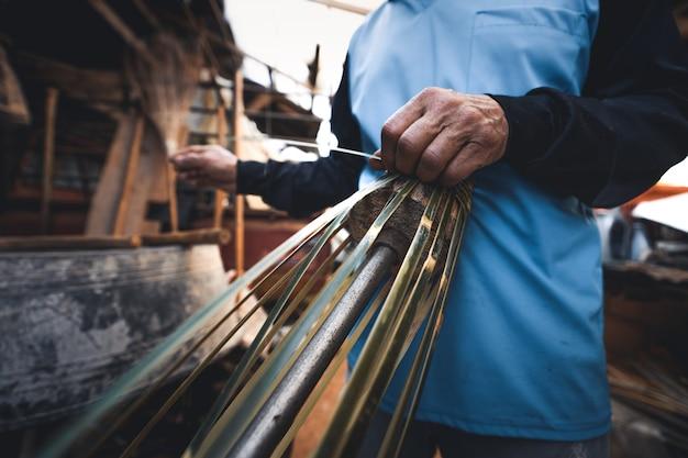 Mains tissant des paniers en bambou à la maison, font un panier