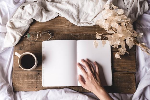 Mains touchant un livre sur une planche de bois avec des lunettes et des fleurs séchées