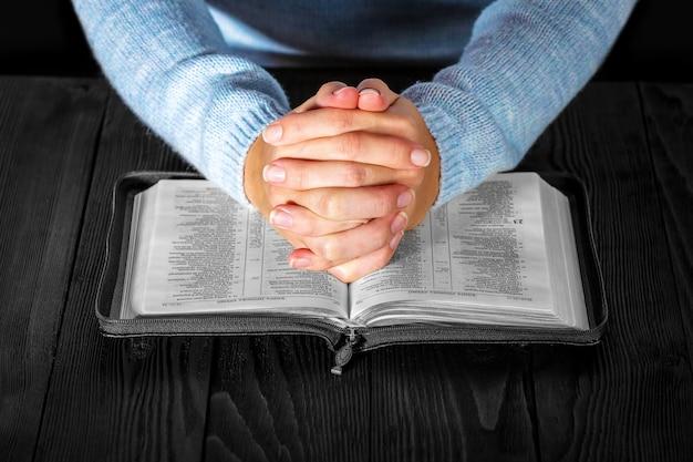 Mains en tournant la page d'une bible