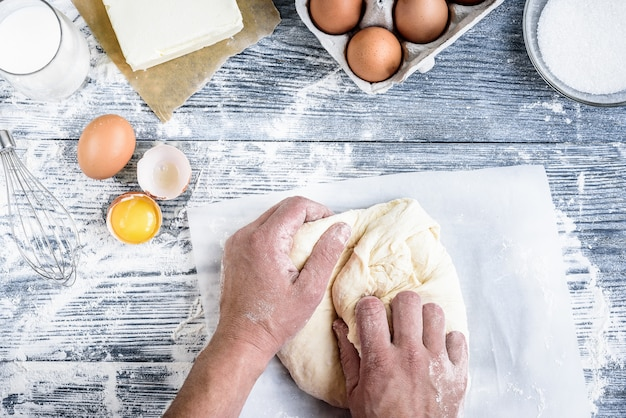 Mains travaillant avec du pain, des petits pains, des pizzas ou des tartes faisant la recette de la préparation de la pâte, la nourriture à plat sur fond de table en bois gris