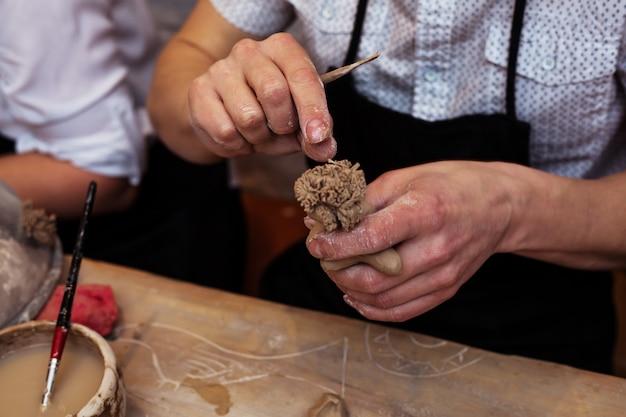Mains travaillant et finissant la sculpture avec de l'argile sur une table en bois en atelier