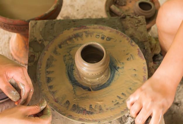 Mains travaillant la machine d'argile travaillant la main