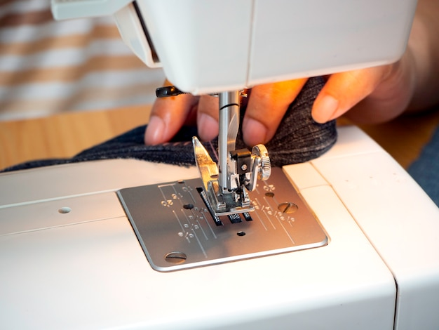 Mains travaillant sur la machine à coudre