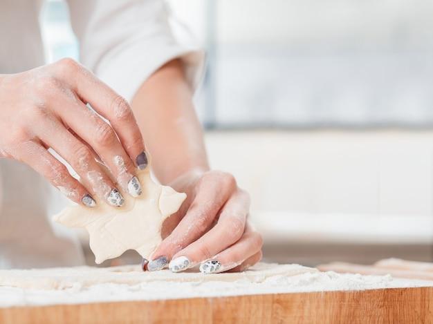 Mains travaillant avec de la pâte à préparer des cookies
