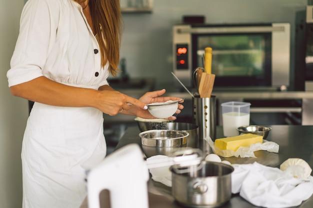 Mains travaillant avec la recette de la préparation de la pâte pain pizza ou tarte faisant des ingrédients de cuisson des gâteaux