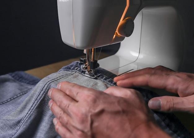 Mains travaillant avec un tissu denim sur un concept de petite entreprise en gros plan sur une machine à coudre