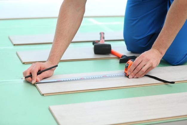 Mains de travailleur masculin installant un revêtement de sol stratifié