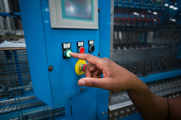 Mains de travailleur d'usine en appuyant sur un bouton vert sur le tableau de commande