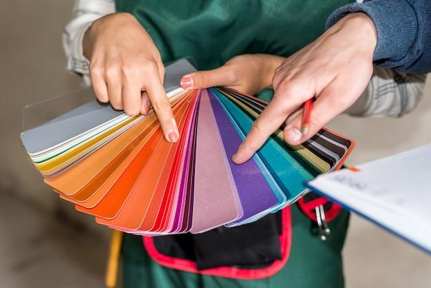 Les mains des travailleurs choisissant la couleur pour la peinture sur l'échantillonneur