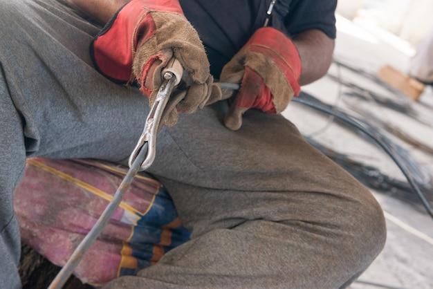 Les Mains Des Travailleurs De La Construction Redressent La Tige Métallique. De Vraies Personnes Franches Photo Premium