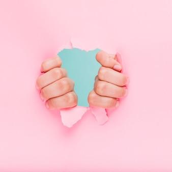 Les mains à travers un trou de papier