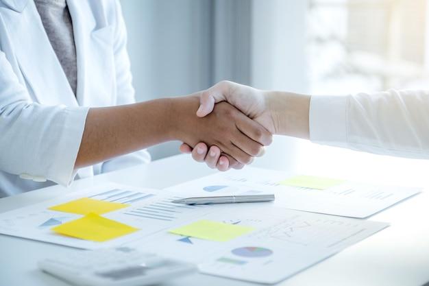 Mains tremblantes après la réunion de l'équipe de femme d'affaires et d'hommes d'affaires pour planifier des stratégies visant à augmenter les revenus de l'entreprise. faites un brainstorming sur l'analyse graphique et discutez du succès de la nouvelle cible.