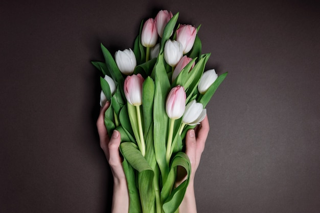 Mains avec des tulipes. le concept de la pose de fleurs aux héros tombés