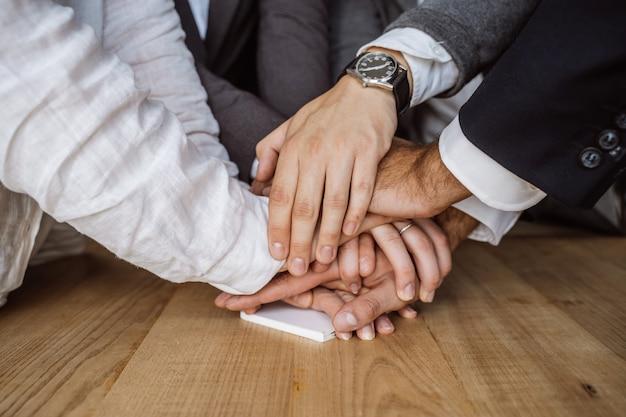 Mains unies de l'équipe des affaires sur fond d'espace de travail
