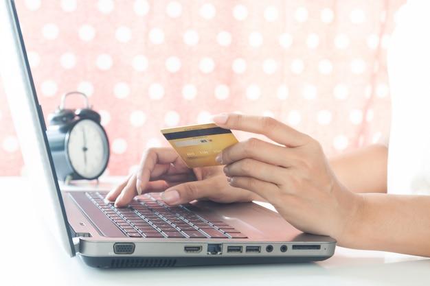Mains utilisant un ordinateur portable et une carte de crédit. technologie intelligente. shopping en ligne