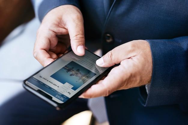 Mains utilisant un smartphone lisant des nouvelles à l'écran