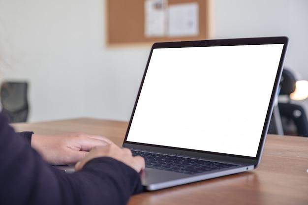 Mains en utilisant et en tapant sur un ordinateur portable avec un écran de bureau blanc vierge alors qu'il était assis au bureau
