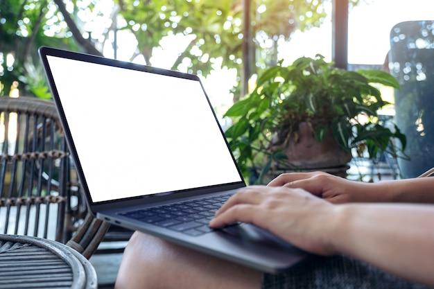 Mains en utilisant et en tapant sur un ordinateur portable avec un écran de bureau blanc vierge alors qu'il était assis à l'extérieur