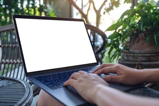 Mains en utilisant et en tapant sur un ordinateur portable avec un écran de bureau blanc vierge tout en étant assis à l'extérieur