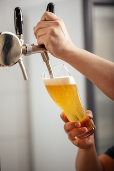 Mains versant de la bière pression dans un verre