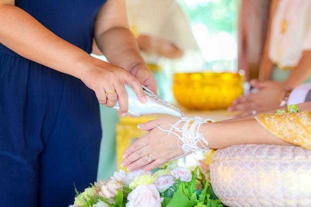 Mains versant de l'eau de bénédiction dans les bandes de la mariée, mariage thaïlandais.