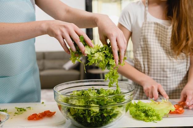 Les mains versent les verts pour la salade dans un bol