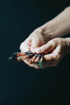 Mains de vieille artiste féminine tenant des pinceaux sales en désordre avec différentes peintures dans un studio d'art. concept de mode de vie et de passe-temps